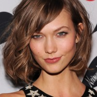 Karlie Kloss Wild Soft Curly Bob Hairstyle with Long Side Swept Bangs