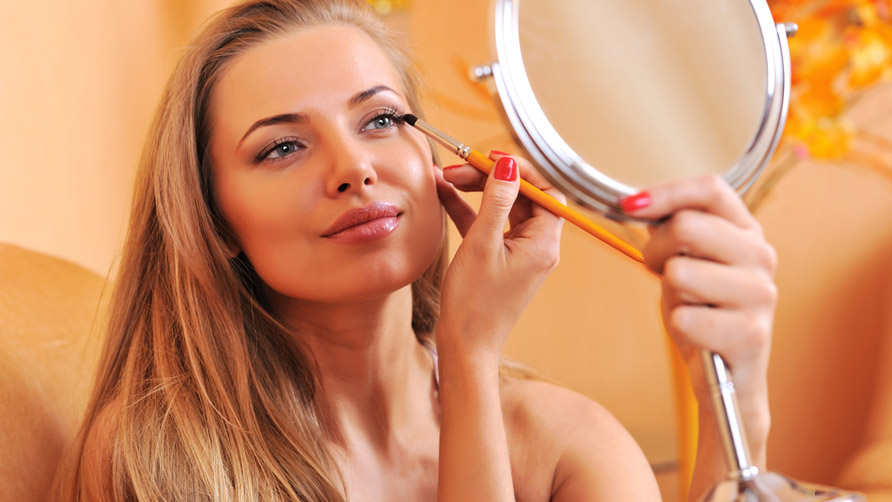 Young-beautiful-woman-applying-make-up